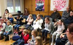 Foto van de luisterende kinderen en (groot)ouders