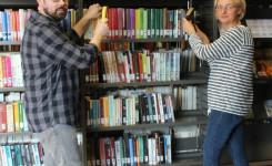 Foto van Robby en Els die bezig zijn het herschikken van de boeken.
