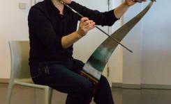 Foto van Jef Aerts terwijl hij de zingende zaag bespeelt