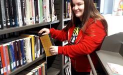 Foto van stagiaire Elien Poelmans terwijl ze ingeleverde boeken weer op hun plaats zet.