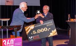 Een foto van Jacob Vis die de cheque voor de Gouden Vleermuis ontvangt