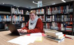 Foto van auteur Inge Verbruggen terwijl ze een boek schrijft in de bib
