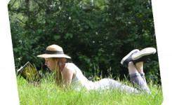 Foto van een lezende jongedame, liggend in het lange gras