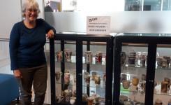 Foto van Mieke Meskens naast de met haar koffiemokken gevulde tentoonstellingskasten