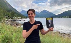 Foto van Gaea Schoeters met een exemplaar van haar boek 'Trofee ' in de hand.