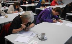 Foto van de ijverig schrijvende deelnemers aan Het Groot Dictee Heruitgevonden