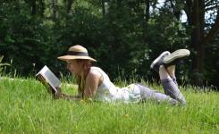 Foto van een jongedame een boek lezend terwijl ze languit in het gras ligt