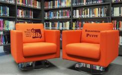 Sfeerfoto van twee oranje zetels in de bib
