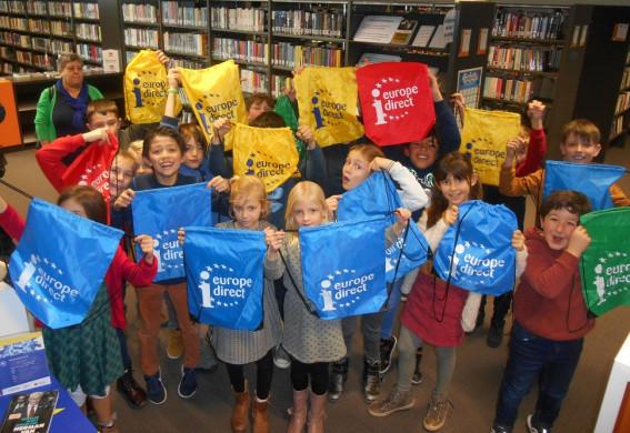 Foto van de kinderen van het derde leerjaar in de bib