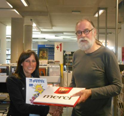 Foto van vrijwilligster Patricia De Smet die gevierd wordt naar aanleiding van het 20.000ste boek dat ze plastificeert.