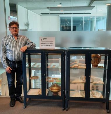 Foto van Herwig De Lannoy naast de tentoonstellingskast met sigarenbandjes