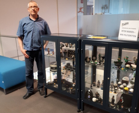 Peter Mariën en de met miniatuurpolitiepetten gevulde tentoonstellingskasten