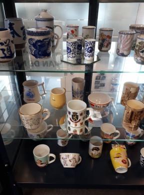 Foto van de met koffiemokken gevulde tentoonstellingskasten.