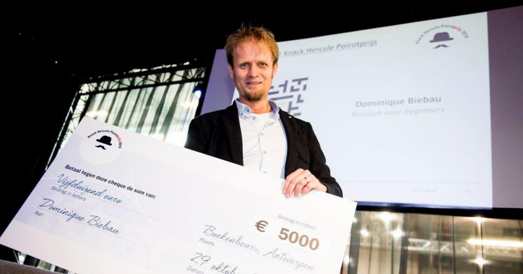Foto van laureaat Dominique Biebau die zijn cheque in ontvangst neemt