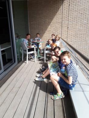 Foto van lezende schoolkinderen op het terras van de bib