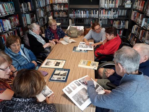 Foto van in boeken kijkende bewoners van een woonzorgcentrum op bezoek in de bib
