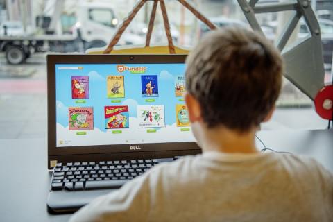 Foto van een jongen voor een laptop met op het scherm een hele reeks fundels
