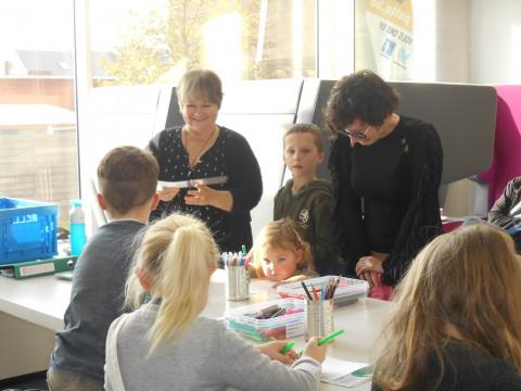 Voorleesvrijwilliger Marleen Feyaerts knutselt met de kinderen een bladwijzer.